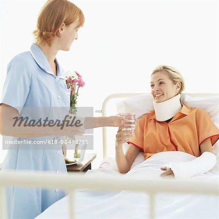 weibliche Krankenschwester geben ein Glas Wasser zu einer Frau trägt eine Halskrause und einen Arm umgewandelt