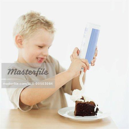 Seitenansicht eines jungen Spritzen auf ein Stück Schokolade Kuchen mit Schlagsahne
