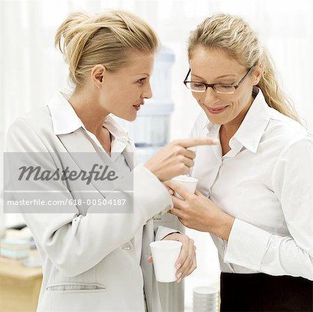 Porträt von zwei junge Unternehmerinnen schwatzen am Arbeitsplatz