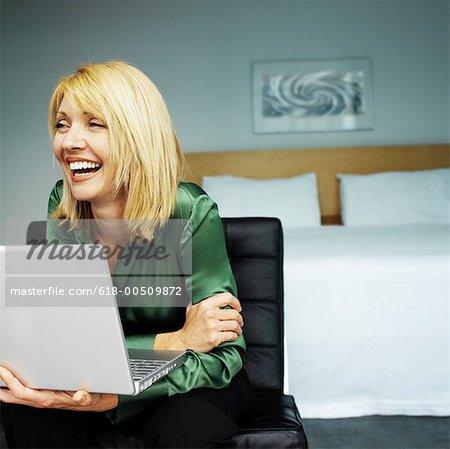 Frau sitzt in einem Schlafzimmer lachen beim Laptop benutzen