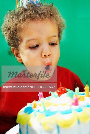 Junge Ausblasen der Kerzen auf der Geburtstagstorte