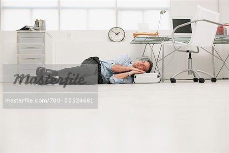 Homme d affaires de dormir sous le bureau photographie de stock