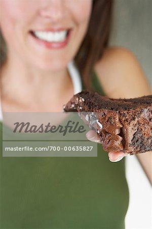 Frau hält Schokoladenkuchen