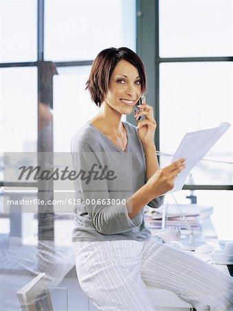 Porträt einer geschäftsfrau Gespräch auf ein Mobiltelefon in einem Büro