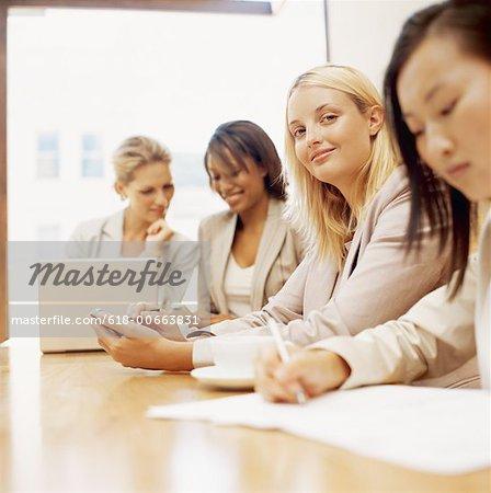 vier Geschäftsfrauen sitzen an einem Tisch in einem Büro