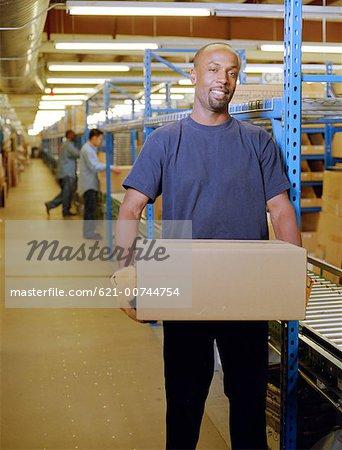 Happy worker lifting carton