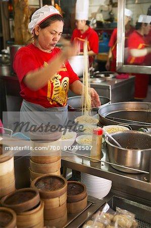 Female Chef Putting Noodles Into Bowls, Bangkok Thailand