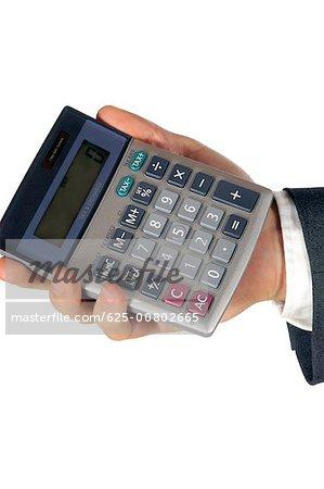 Close-up of a businessman holding a calculator
