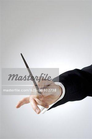 Gros plan des mains du chef d'orchestre, tenant un bâton
