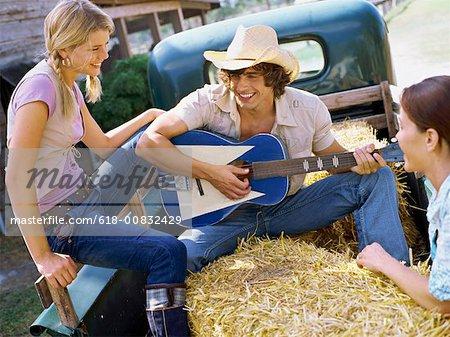 Jeunes femmes en écoutant un jeune homme jouant de la guitare