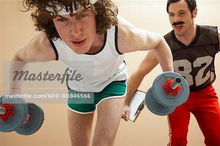 Mann Aufhebung Gewichte mit Personal Trainer