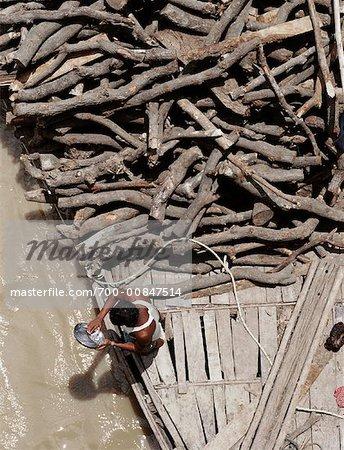 Homme sur le bateau transportant du bois, Varanasi, Inde