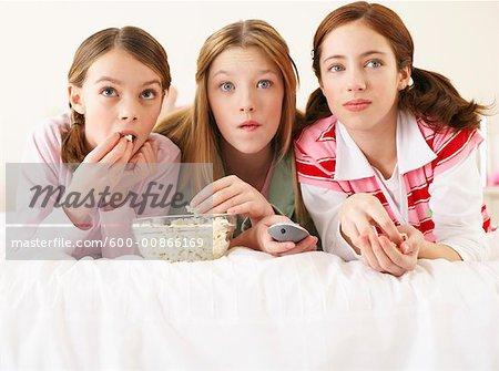 Girls Lying on Bed, Eating Popcorn