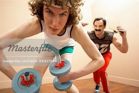 Mann Aufhebung Gewichte, Personal-Trainer im Hintergrund