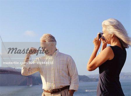 Woman Photographing Man by Golden Gate Bridge, San Fransisco, California, USA