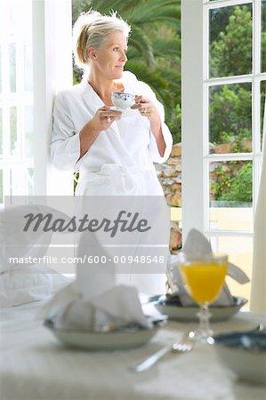 Frau trinkt Kaffee am Morgen auf Terrasse