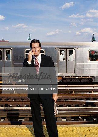 Homme d'affaires sur le quai de métro, parler au téléphone cellulaire