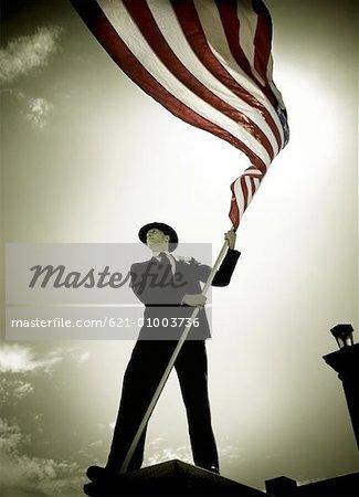 Homme en costume tenant le drapeau américain