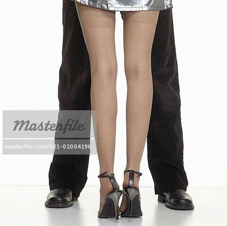 Vue arrière de femme debout entre les jambes de l'homme