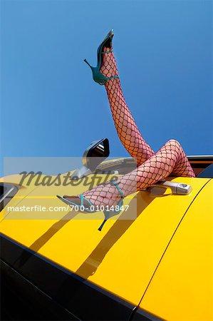 Jambes de femme suspendus hors de la fenêtre de voiture