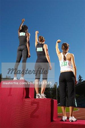 Champion Athletes Standing on Podium