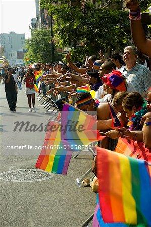 Grand groupe de personnes agitant des drapeaux droits gay à une parade gay