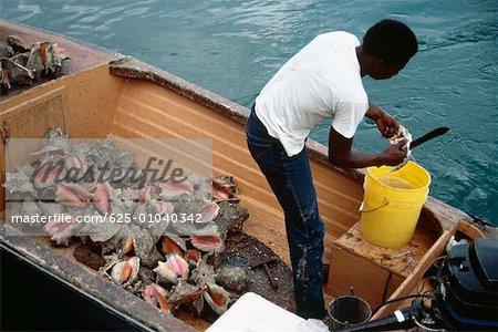 Vue latérale d'un pêcheur traversant ses prises dans le port de Nassau, Nassau, Bahamas