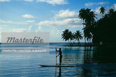 Silhouette d'un homme ramant un bateau dans une mer calme, Sainte-Lucie