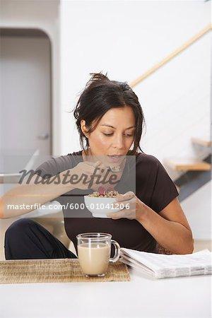 Frau lesen beim Essen Müsli