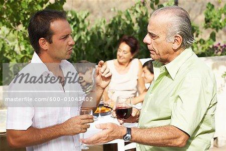 Père et fils parlant, avec d'autres membres de la famille en arrière-plan