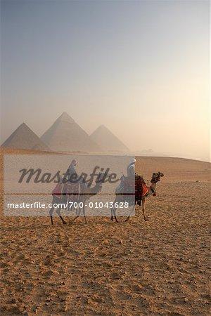Cavaliers sur des chameaux, des pyramides de Giza Giza, Égypte