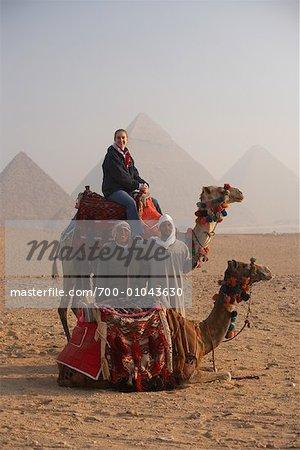Femme qui pose avec les pilotes dromadaires et chameaux, Giza, Égypte