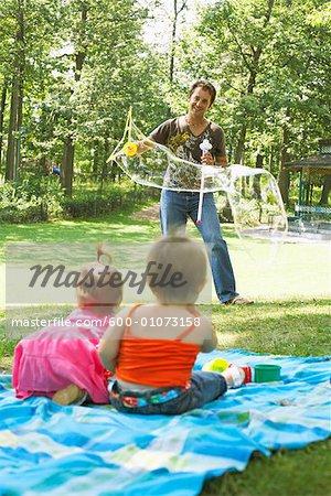 Père Blowing Bubbles tandis que bébés Watch