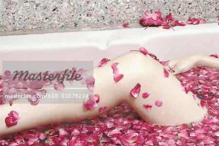 Gros plan des jambes de la femme dans une baignoire remplie de pétales de fleurs