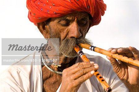 Close-up of a senior man playing two flutes, Pushkar, Rajasthan, India