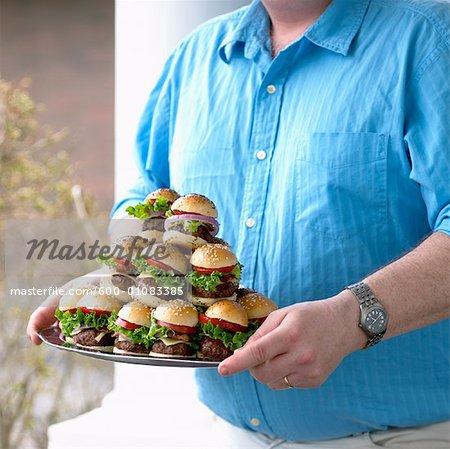 Man Carrying Plate of Small Hamburgers