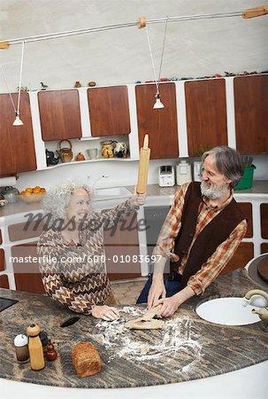 Frau necken Mann mit Nudelholz in Küche