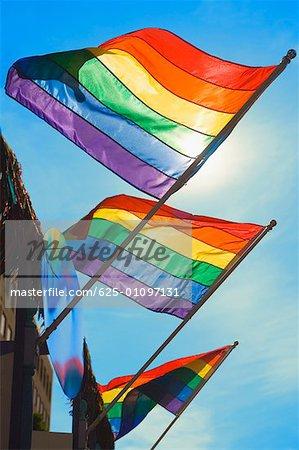 Vue d'angle faible de trois indicateurs de la gay pride flottant sur un bâtiment