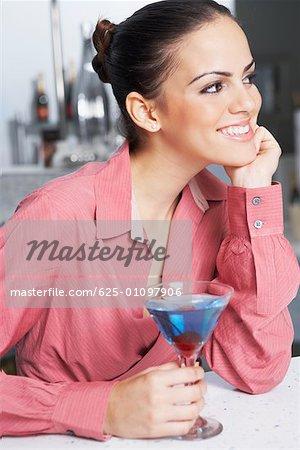 Gros plan d'une femme d'affaires avec un verre de cocktail souriant dans un bar