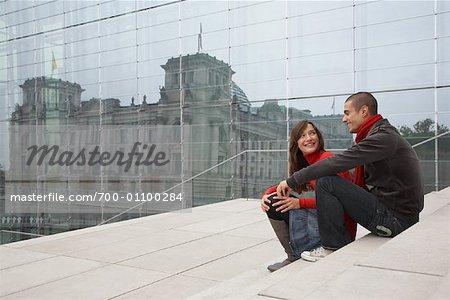 Couple assis sur les marches près du Reichstag, Berlin, Allemagne