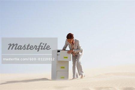 Femme d'affaires et classeurs dans le désert