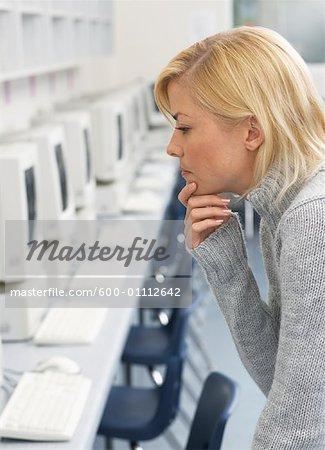Femme regardant ordinateur en salle informatique