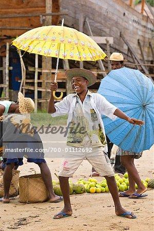 Junge mit Sonnenschirm am Dorf Markt, Maroantsetra, Madagaskar
