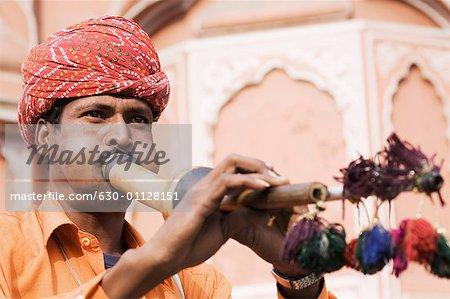 Close-up of a snake charmer playing a wind instrument, Hawa Mahal, Jaipur, Rajasthan, India