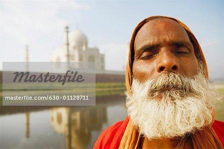 Close-up of a priest meditating on the riverbank with his eyes closed, Taj Mahal, Agra, Uttar Pradesh, India