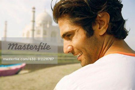 Rear view of a young man standing on the riverbank, Taj Mahal, Agra Uttar Pradesh, India
