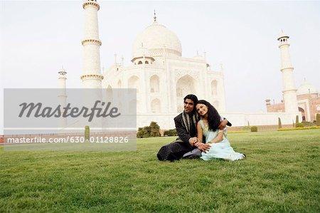Young couple sitting in front of a mausoleum, Taj Mahal, Agra, Uttar Pradesh, India