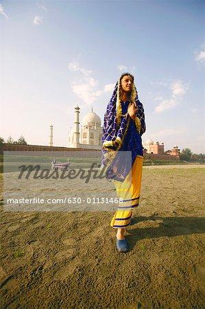 Low angle view of a young woman walking on the riverbank, Taj Mahal, Agra, Uttar Pradesh, India