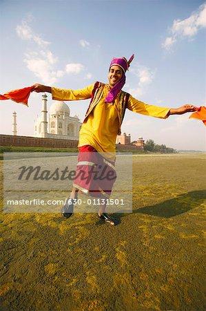Portrait of a young man dancing on the riverbank, Taj Mahal, Agra Uttar Pradesh, India