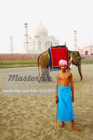 Young man standing in front of an elephant near a mausoleum, Taj Mahal, Agra, Uttar Pradesh, India